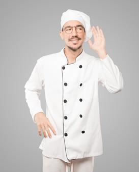 Gelukkige jonge chef-kok die en een gebaar van het proberen om iets te horen glimlacht maakt