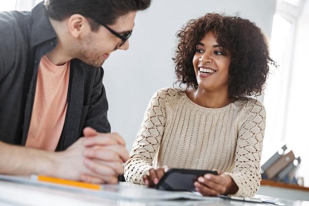 Gelukkige jonge collega's die samen smartphone gebruiken terwijl ze bij de tafel op kantoor zitten