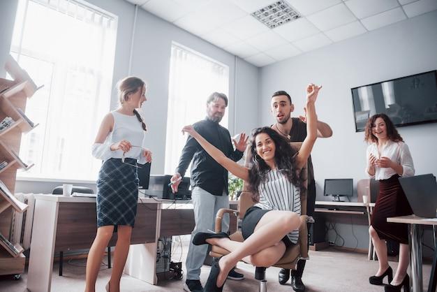 Gelukkige jonge collega's glimlachen en hebben plezier op het creatieve kantoor.