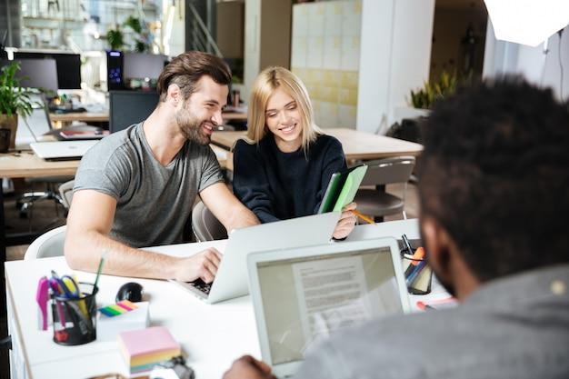 Gelukkige jonge collega's zitten in kantoor naaiatelier