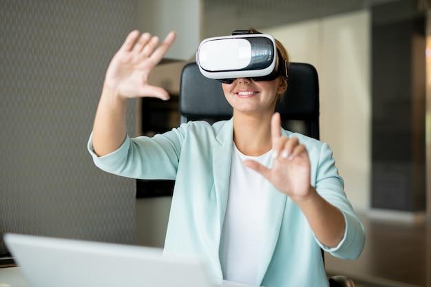 Gelukkige jonge creatieve vrouw in smartcasual wijzend op virtuele weergave tijdens het maken van de presentatie
