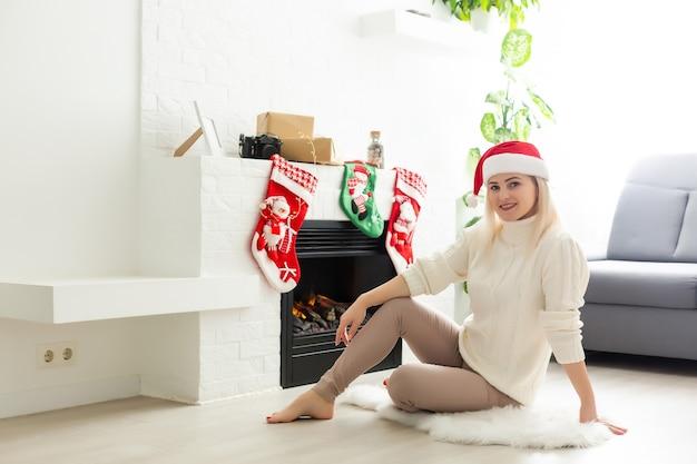 Gelukkige jonge dame bij de open haard. kerstmis nieuwjaar concept.