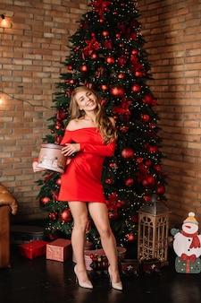 Gelukkige jonge dame die gift loskoppelt dichtbij de kerstboom