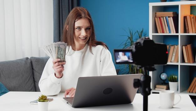 Gelukkige jonge dame filmen videoblog zittend aan tafel met laptop erop en bos geld tonen