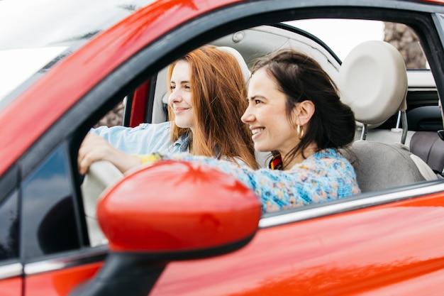 Gelukkige jonge dames die in auto zitten