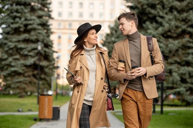 Gelukkige jonge dates in beige vrijetijdskleding praten en koffie drinken onderweg in een stedelijke omgeving tegen het bouwen van een hedendaagse universiteit