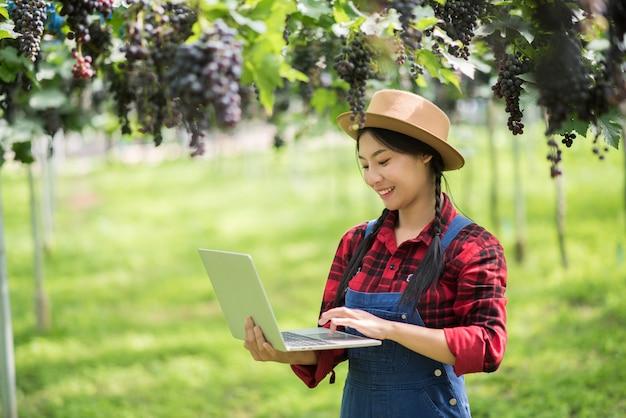 Gelukkige jonge de holdingstakken van de vrouwentuinman van rijpe blauwe druif