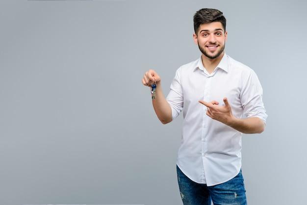 Gelukkige jonge die mens met sleutels over grijze achtergrond wordt geïsoleerd