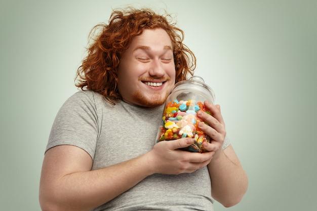 Gelukkige jonge dikke zwaarlijvige man die vreugdevol glimlacht, de ogen gesloten houdt en zich verheugt over de glazen pot met lekkernijen