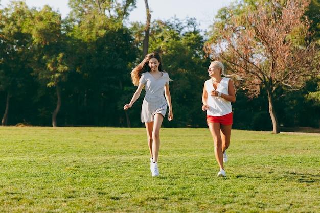 Gelukkige jonge dochter met lang bruin haar en haar moeder rennen samen in het park, sport in de zomer zonnige tijd. vrouw en meisje buitenshuis. familie, lifestile concept.