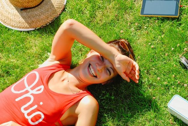 Gelukkige jonge donkerbruine vrouw die aan de muziek openlucht op een de zomerdag luistert