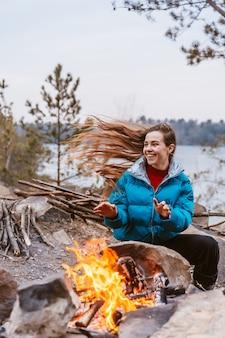 Gelukkige jonge donkerbruine vrouwenzitting naast vuur