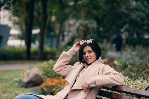 Gelukkige jonge donkerbruine zitting op een parkbank