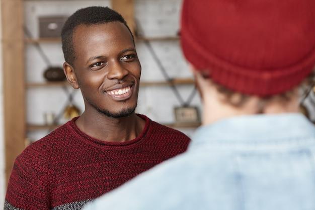 Gelukkige jonge donkere man die vrolijk lacht en naar zijn onherkenbare stijlvolle vriend kijkt