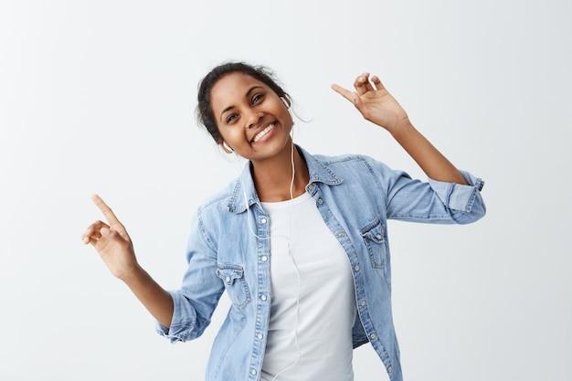 Gelukkige jonge donkere vrouw in blauw overhemd met charmante aantrekkelijke glimlach, haar vingers wijzend met een gelukkige blik, genietend van haar favoriete liedje en dansend.