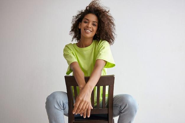 Gelukkige jonge donkere vrouw poseren met wild krullend haar, zittend op een stoel met gekruiste handen en breed glimlachend