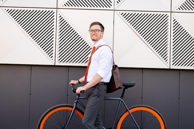 Gelukkige jonge elegante man die door de muur van moderne architectuur staat terwijl hij na een werkdag de fiets gaat gebruiken om naar huis of naar het café te gaan