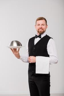 Gelukkige jonge elegante ober in zwart vest en vlinderdas die witte handdoek en glazen kap met voedsel houdt terwijl hij voor camera staat