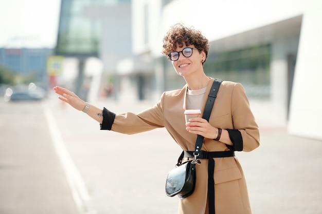 Gelukkige jonge elegante vrouw met een glas koffie die over de weg staat en een taxi neemt tegen modern gebouw in stedelijke omgeving