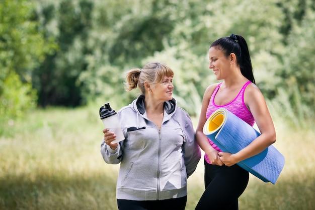 Gelukkige jonge en oude vrouwen in sportkleding praten in het park