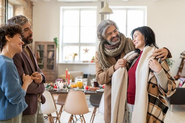 Gelukkige jonge en volwassen stellen in vrijetijdskleding die elkaar glimlachend aankijken en praten in de woonkamer tijdens een bezoek voor kerstnacht