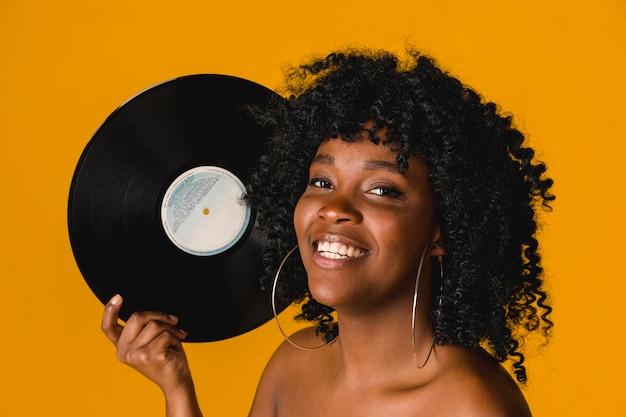 Gelukkige jonge etnische vrouw die vinylplaat op heldere achtergrond houdt