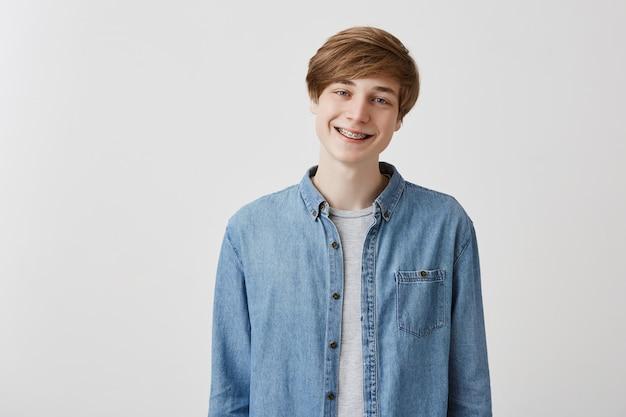 Gelukkige jonge europese man met blond haar en blauwe ogen, lacht breed met beugels, verheugt zich om vrienden te ontmoeten, heeft een interessant gesprek, deelt nieuws met elkaar, vertelt grappige levensverhalen.