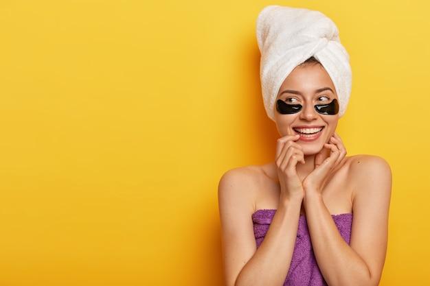 Gelukkige jonge europese vrouw raakt de huid zachtjes aan, kijkt opzij, past schoonheid onder de ogen toe, gewikkeld in een handdoek, kijkt aan de linkerkant