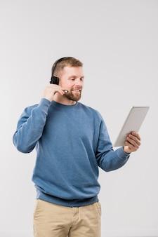 Gelukkige jonge exploitant met hoofdtelefoon en touchpad die cliënten online raadplegen terwijl zij afzonderlijk beeldscherm bekijken