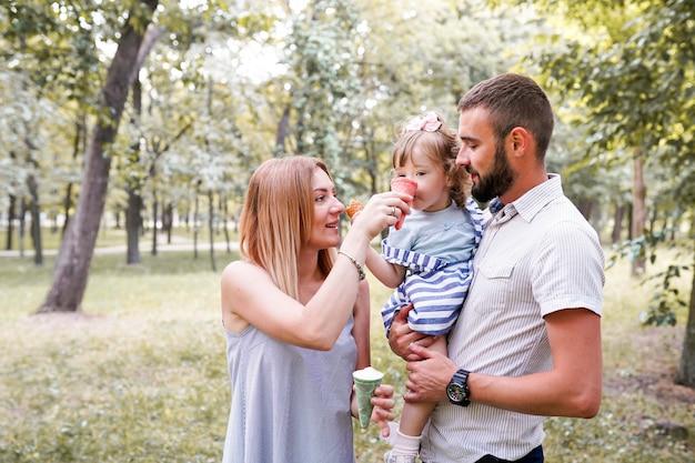 Gelukkige jonge familie die roomijs eet en pret buiten heeft