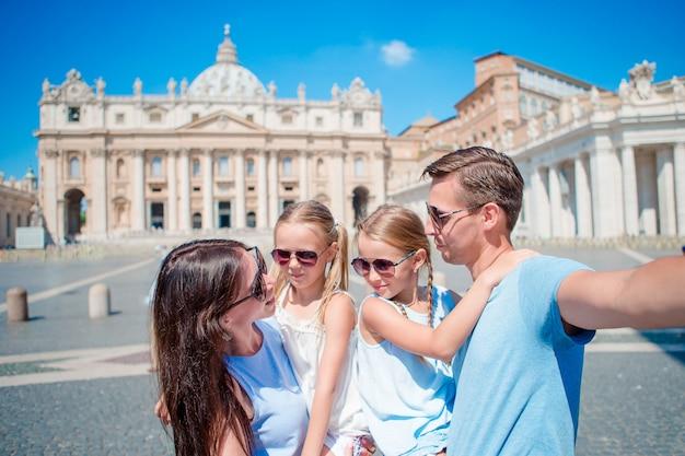 Gelukkige jonge familie die selfie bij st. peter basiliekkerk nemen in de stad van vatikaan, rome. gelukkige reisouders en jonge geitjes die selfie fotobeeld op europese vakantie in italië maken.