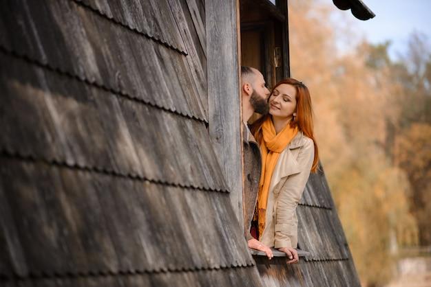 Gelukkige jonge familie gluren uit de ramen van een groot houten huis. het concept van het kopen van een huis, het huren van een huis, voor een gezin