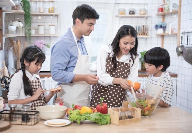 Gelukkige jonge familie hebben vrije tijd in de keuken, vader helpt moeder koken, dochter en zoon eten yam en brood.