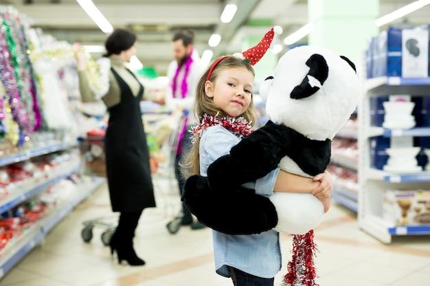 Gelukkige jonge familie in de supermarkt kiest cadeaus voor het nieuwe jaar