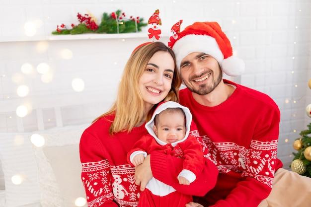 Gelukkige jonge familie moeder vader en baby in rode truien onder de kerstboom op het bed thuis vieren nieuwjaar of kerstmis door elkaar te kussen en te knuffelen
