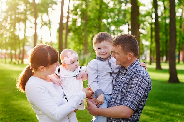 Gelukkige jonge familie wandelingen in het park van de zomer
