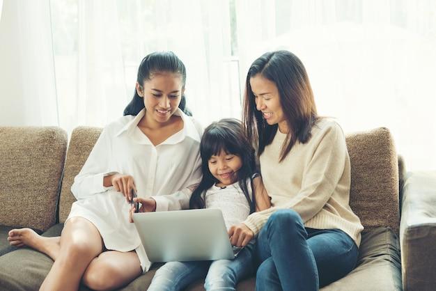 Gelukkige jonge familie zittend op een bank en kijken naar laptop in huis