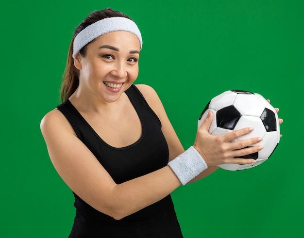 Gelukkige jonge fitnessvrouw met hoofdband die voetbal vasthoudt en vrolijk glimlacht