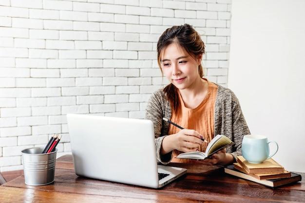 Gelukkige jonge freelancer-vrouw die aan computerlaptop werken