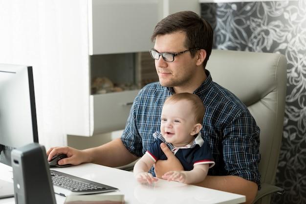 Gelukkige jonge freelancer-zakenman die thuis werkt en voor zijn baby zorgt