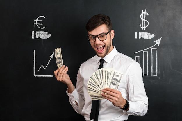 Gelukkige jonge gebaarde mens die in glazen bos van geld houden