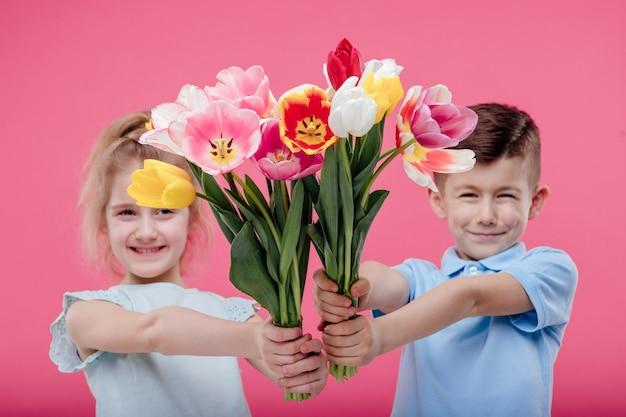 Gelukkige jonge geitjes die bloemen geven