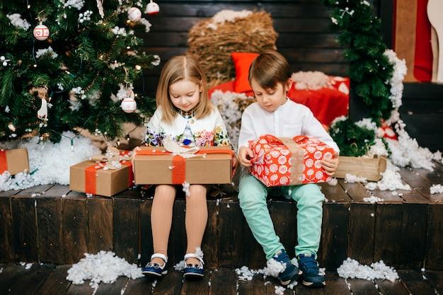 Gelukkige jonge geitjes die giftdozen in studio met cristmasboom en nieuwe jaardecoratie openen.
