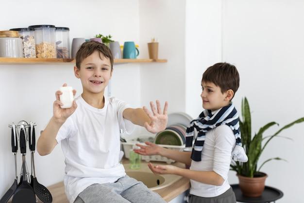 Gelukkige jonge geitjes die hun schone handen tonen terwijl het houden van zeep