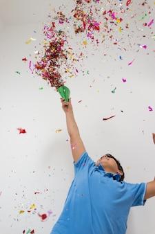 Gelukkige jonge geitjes die partij met blazende confettien vieren