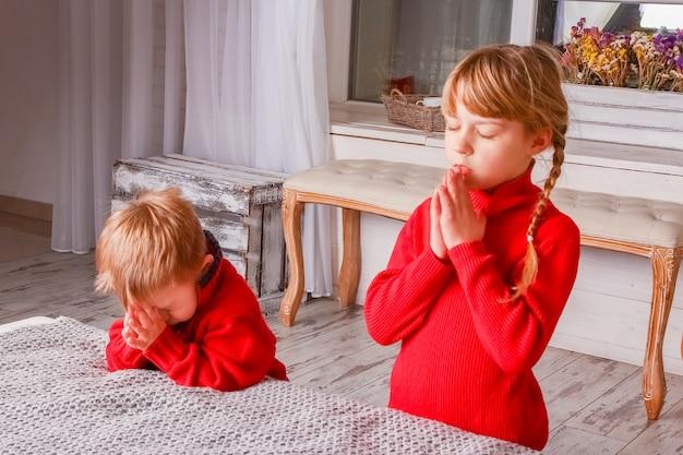 Gelukkige jonge geitjes die thuis voor kerstmis bidden