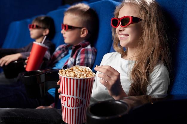 Gelukkige jonge geitjes kijken naar film in 3d-bril in de bioscoop.