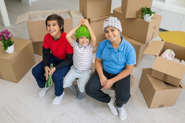 Gelukkige jonge geitjes met dozen bij nieuw modern huis