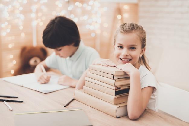 Gelukkige jonge geitjes met gestapelde schoolboeken aan de balie