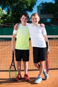 Gelukkige jonge geitjes op het tennisveld